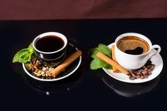 Café noir dans des tasses noires et blanches avec des épices Photo stock