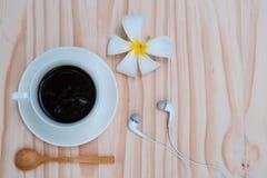 Café noir dans la tasse blanche avec la fleur blanche de plumeria sur b en bois Photographie stock