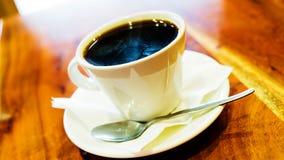 Café noir dans la tasse blanche sur la table en bois brune Photo libre de droits
