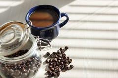 Café noir dans la tasse bleue sur la table blanche avec des ombres des abat-jour Photographie stock