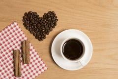 Café noir dans une tasse et soucoupe avec des bâtons de cannelle et des grains de café Photos libres de droits