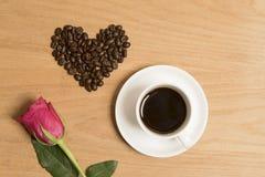 Café noir dans une tasse et soucoupe avec une rose rouge et des grains de café Photographie stock