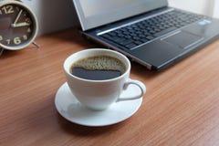 Café noir dans une tasse et un ordinateur portable blancs photo stock