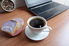 Café noir dans une tasse, un pain, et un ordinateur portable blancs photos stock