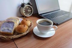 Café noir dans une tasse, un pain, et un ordinateur portable blancs image libre de droits