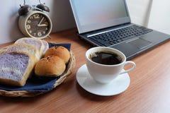 Café noir dans une tasse, un pain, et un ordinateur portable blancs photos libres de droits