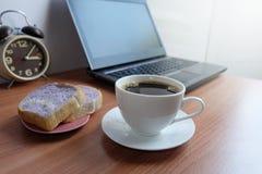 Café noir dans une tasse, un pain, et un ordinateur portable blancs photographie stock libre de droits