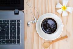Café noir et carnet ou ordinateur portable d'ordinateur avec le headpho de dans-oreille Photos libres de droits