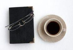 Café noir et livre noir Photo stock
