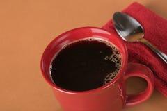 Café noir fraîchement versé dans une tasse rouge Photo stock