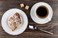 Café noir, sucre grumeleux et morceau de gâteau dans le plat Photos libres de droits
