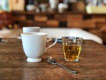 Café noir sur la belle tasse blanche et le verre chaud de thé, cuillère inoxydable sur la table en bois de vintage photographie stock libre de droits