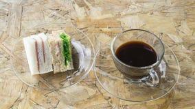 Café noir sur la table en bois avec le sanwich Photo libre de droits
