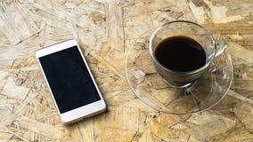 Café noir sur la table en bois avec le téléphone Photographie stock