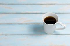 Café noir sur le bois de couleur de bleu de ciel Photographie stock