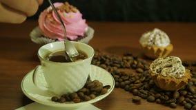 Café nos copos brancos, nos bolos e em uma dispersão de feijões de café na tabela video estoque