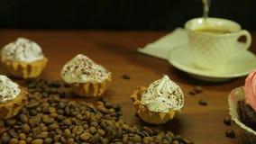Café nos copos brancos Mulher que agita com uma colher, os bolos e uma dispersão de feijões de café na tabela filme
