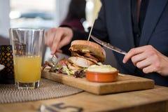 Café novo de Having Sandwich In do homem de negócios fotografia de stock royalty free