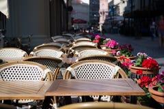 Café o restaurante de la calle con las tablas, las sillas y las flores Fotos de archivo