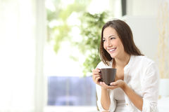 Café o té de consumición de la mujer en casa Imagenes de archivo
