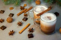 Café ou chocolate quente do cacau da bebida do Natal com leite em um copo pequeno Ramo de árvore do abeto, porcas, anis de estrel Imagem de Stock Royalty Free