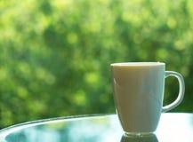 Café ou thé dans la grande tasse blanche sur la table en verre, fond de nature dans le jardin, vue de côté photo libre de droits