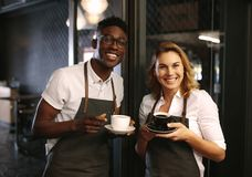 Café owners at their coffee shop holding coffee cups. Male and female barista standing at the entrance of coffee shop holding coffee cups. Happy coffee Royalty Free Stock Photography