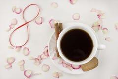 Café, pétalas cor-de-rosa, canela, café vermelho do número oito imagem de stock