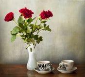 Café para dois e um vaso de rosas vermelhas Imagem de Stock