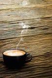 Café parfumé de cappuccino avec de la fumée sur le vieux plancher en bois Photo stock