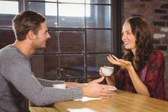 Café parlant et potable de couples de sourire Photographie stock