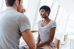 Café parlant et potable de jeunes couples heureux en café Images libres de droits