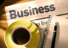 Café, periódico, pluma y cuaderno en el escritorio Fotos de archivo