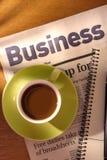 Café, periódico y cuaderno en el escritorio Fotos de archivo