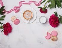 Café, pivoines roses et macarons sur la table de marbre Photos stock
