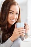 Café potable attrayant de jeune femme à la maison photo stock