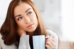 Café potable attrayant de jeune femme à la maison photographie stock