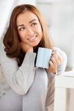 Café potable attrayant de jeune femme à la maison photo libre de droits