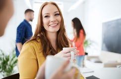 Café potable d'équipe créative heureuse au bureau Photos stock