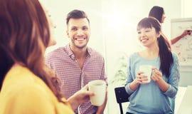 Café potable d'équipe créative heureuse au bureau Images libres de droits