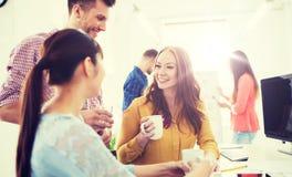 Café potable d'équipe créative heureuse au bureau Images stock