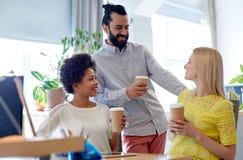 Café potable d'équipe créative heureuse dans le bureau Photos stock