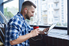 Café potable d'homme élégant et écouter la musique Photo libre de droits