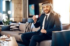 Café potable d'homme d'affaires arabe sur le divan à la chambre d'hôtel Photographie stock libre de droits