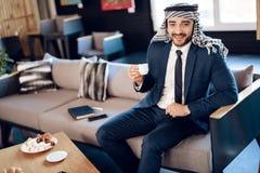 Café potable d'homme d'affaires arabe sur le divan à la chambre d'hôtel Photos libres de droits