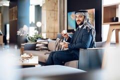 Café potable d'homme d'affaires arabe sur le divan à la chambre d'hôtel Photo stock