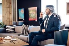 Café potable d'homme d'affaires arabe sur le divan à la chambre d'hôtel Image libre de droits