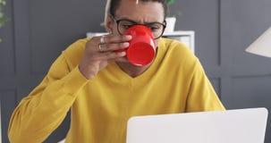 Café potable d'homme d'affaires tout en travaillant sur l'ordinateur portable de bureau clips vidéos
