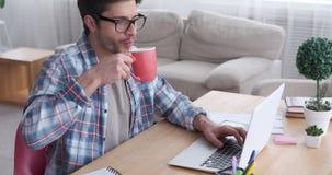 Café potable d'homme d'affaires tout en travaillant sur l'ordinateur portable banque de vidéos