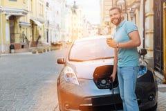 Café potable d'homme bel tout en chargeant la voiture électrique Photo stock